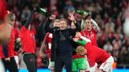 Denmark players celebrate with head coach Kasper Hjulmand after securing their 2022 World Cup spot
