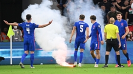 England's players react to a flare being launched onto the field