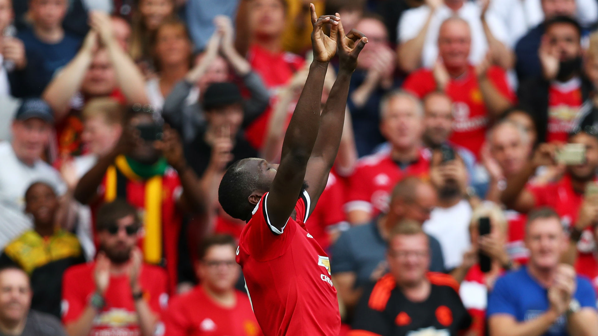 Romelu Lukaku points to the badge after opening his Manchester United account