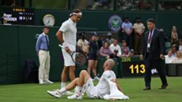 Roger Federer consoles an injured Adrian Mannarino