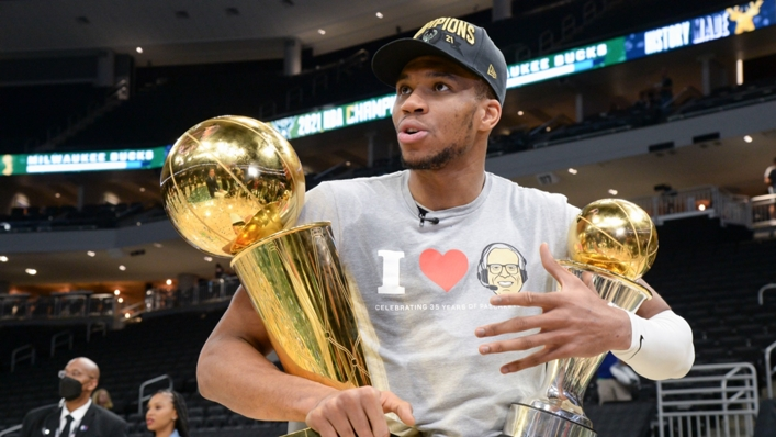 Giannis Antetokounmpo with the Larry O'Brien Trophy and the Bill Russell NBA Finals MVP Award
