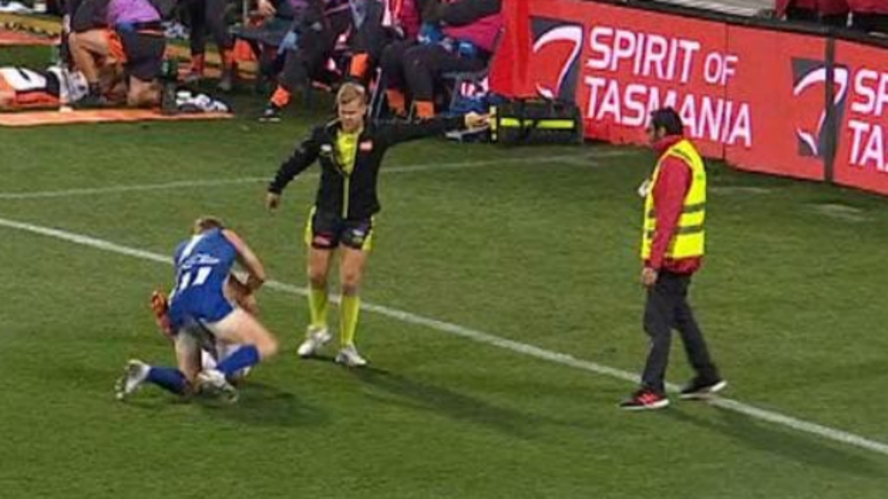 Incredible scenes as security guard walks onto an AFL field to attempt to break up a fight